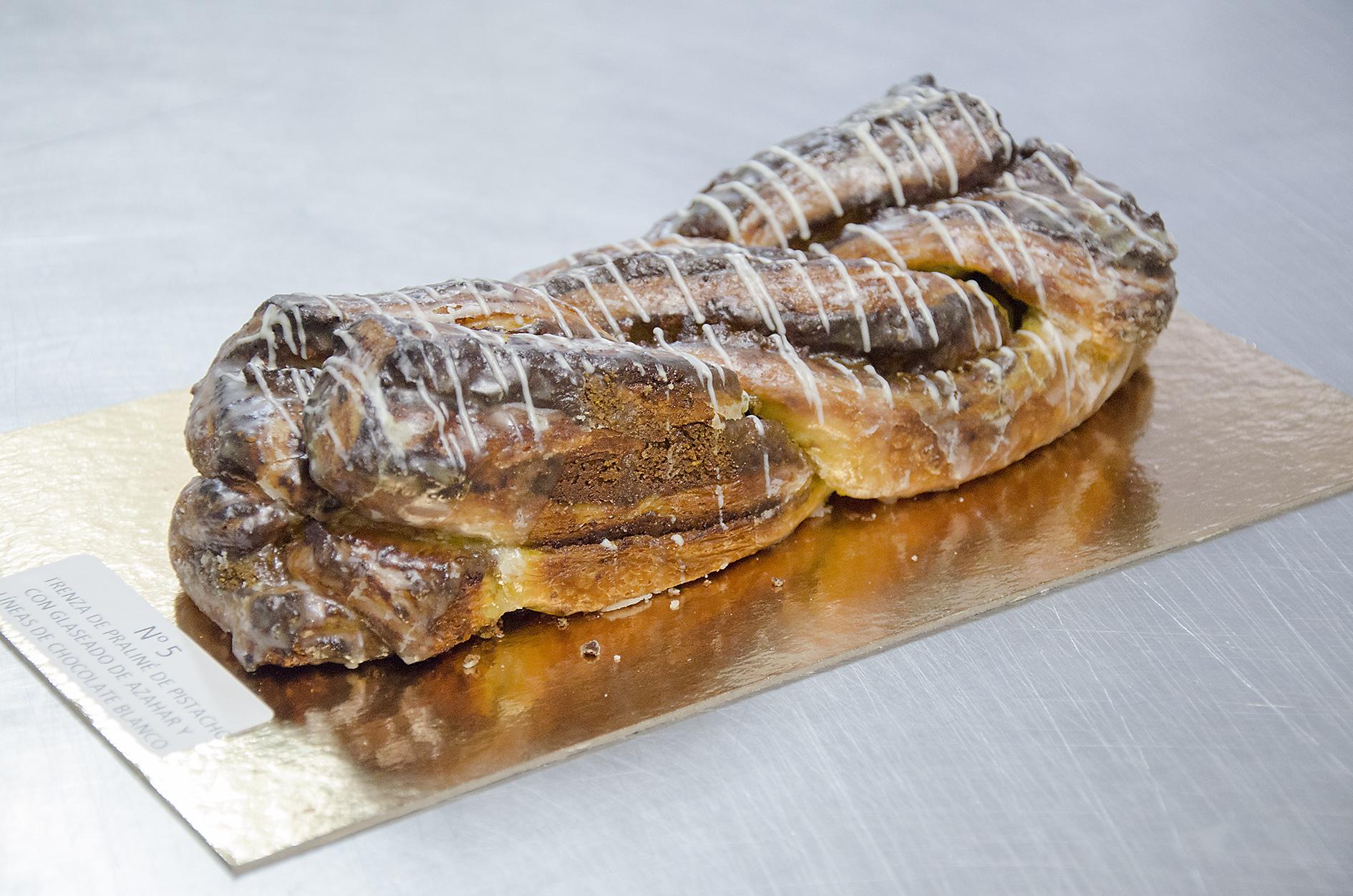 Trenza de praliné de pistacho con glaseado de azahar y líneas de chocolate blanco